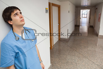 Distressed nurse leaning on wall