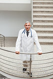 Smiling doctor leaning on the railing of the stairs