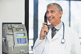 Doctor on a payphone and smiling in hospital