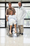Pregnant woman in wheelchair with partner and doctor smiling