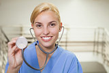 Smiling nurse showing her stethoscope
