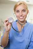 Smiling nurse holding up a stethoscope