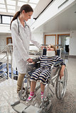 Female doctor smiling at child in wheelchair and neck brace