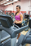 Woman running on a treadmill in a gym concentrating