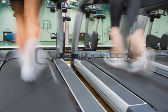Two people running on treadmills