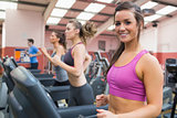 Smiling woman on a treadmill in the gym with people