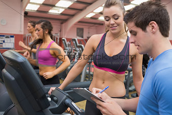 Trainer helping a woman in a gym