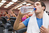 Man drinking water in the gym with towel around neck