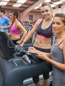 Happy woman and instructor in the gym