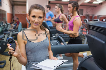 Gym instructor showing stopwatch
