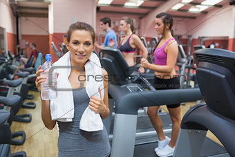 Happy woman drinking water in gym