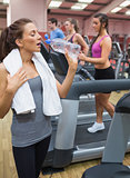 Woman drinking bottle of water in the gym