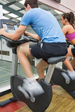 Man and woman riding on an exercise bike