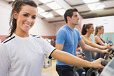 Smiling brunette with other people  on a step machine