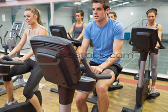 Spinning class riding on an exercise bikes