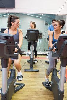 Women talking while training on exercise bike