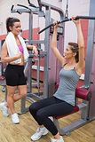 Woman talking to friend using weights machine
