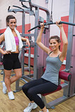 Woman using weights machine with friend beside her