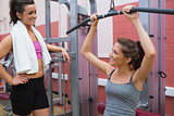 Woman talks to friend using weight machine