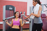 Woman using weights machine talking to friend