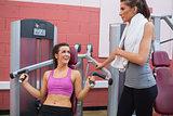 Woman using weights machine talking to friend