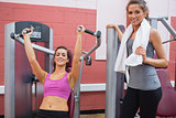 Woman stands beside other woman using weight machine