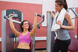 Women using weight machine smiling at friend