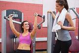 Women using weight machine smiling at friend