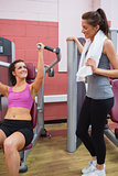Woman using weights machine talking to other woman