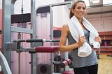 Smiling woman standing beside weight machine