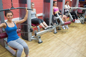 Four women training on weight machines