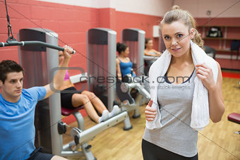 Smiling female trainer wearing towel around her neck