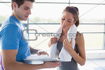 Woman and trainer looking at the fitness program