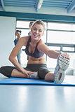 Smiling blonde stretching her leg