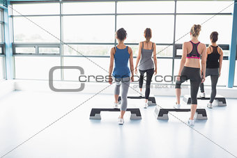 Four women stepping on boards