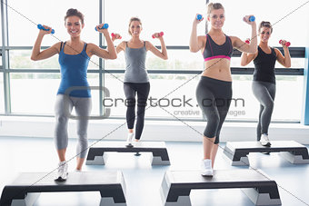 Four women lifting weights while doing aerobics