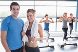 Woman and trainer smiling together in front of aerobics class