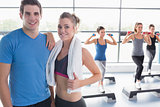 Trainer and woman smiling together while aerobics class taking place
