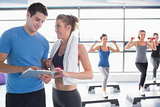 Trainer presenting timetable while aerobics class lifting weights