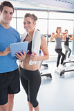 Woman and trainer looking at timetable in aerobics class