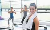 Woman with towel around neck at aerobics class