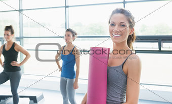 Woman holding a mat and two other women