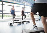 Trainer stepping with aerobics class