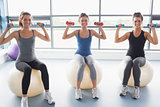 Three smiling women sitting on exercise balls and lifting weights
