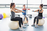Three women lifting weights together on exercise balls