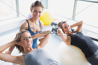 Two women doing sit-ups with trainer