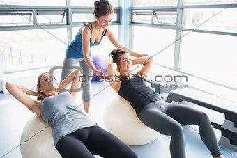 Women doing sit-ups on exercise balls in gym