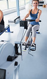 Cheerful brunette training on row machine