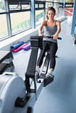 Brunette woman training on row machine