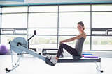 Happy woman training on row machine